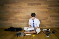 Un homme d'affaires aux pieds nus après jour ouvrable s'assied sur le plancher Photos libres de droits