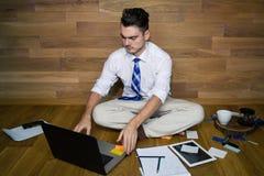 Un homme d'affaires aux pieds nus s'assied sur le plancher contre un mur photographie stock
