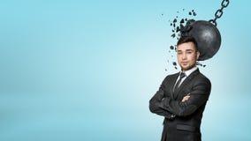 Un homme d'affaires barbu se tient avec les bras pliés tandis qu'une boule de destruction se relie à sa tête Image stock