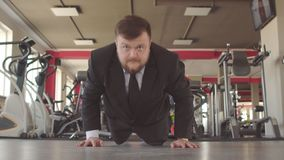 Un homme d'affaires caucasien masculin dans un costume noir exécute des exercices physiques dans un gymnase, les extorque hors du banque de vidéos