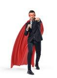 Un homme d'affaires dans un cap rouge de surhomme et un masque se tenant en position de poinçon sur le fond blanc Photos stock