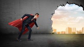 Un homme d'affaires dans un cap rouge se tenant en position courante sur le fond concret avec un trou cassé à la vue de ville Photographie stock libre de droits