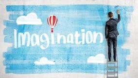 Un homme d'affaires dessine le ciel bleu derrière une imagination de mot avec un ballon à air chaud au lieu d'un point au-dessus  Image stock