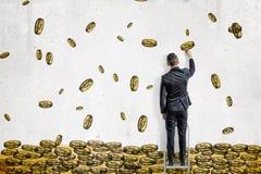 Un homme d'affaires dessine le vol d'or de beaucoup de pièces de monnaie du dollar dans une pile énorme sur un mur blanc illustration stock