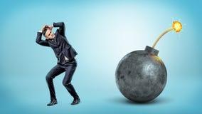Un homme d'affaires effrayé cachant et se couvrant près d'une bombe noire géante de fusible allumé photo libre de droits