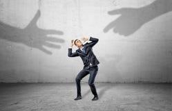 Un homme d'affaires effrayé se cache de deux ombres géantes des mains humaines atteignant à lui Image libre de droits