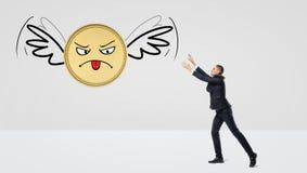 Un homme d'affaires essayant d'attraper une pièce de monnaie d'or qui vole loin sur ses ailes Image libre de droits