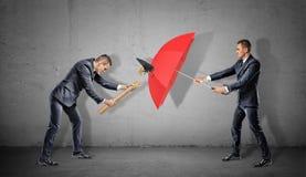 Un homme d'affaires essaye de frapper un autre homme avec un marteau mais il se casse sur un parapluie ouvert rouge Photo stock