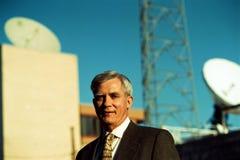 Un homme d'affaires et des paraboloïdes plus anciens de communication par satellites Photos stock