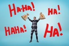 Un homme d'affaires heureux dans un costume rayé de prison et un masque tient des sacs d'argent au-dessus de sa tête près de gran images libres de droits