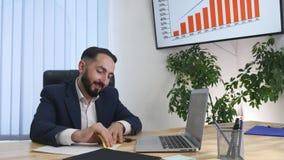 Un homme d'affaires heureux s'asseyant dans son bureau fonctionnant à son ordinateur clips vidéos