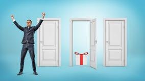 Un homme d'affaires heureux se tient de près de trois portes où seulement un est ouvert avec un boîte-cadeau à l'intérieur Image stock