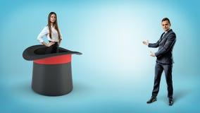 Un homme d'affaires montre une femme d'affaires assurée se tenant à l'intérieur d'un chapeau géant d'illusionnistes sur un fond b images libres de droits