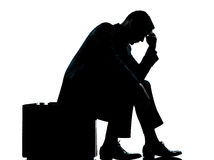 Un homme d'affaires s'asseyant sur la silhouette de valise Image stock