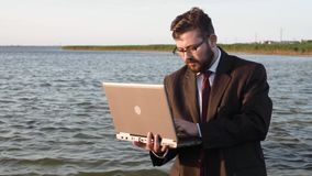 Un homme d'affaires sans pantalon mais avec un ordinateur portable se tient dans l'eau clips vidéos