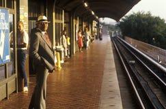 Un homme d'affaires se tient attendant une navette de rail de métro au lever de soleil, aéroport national, Washington, D C Photographie stock libre de droits