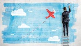 Un homme d'affaires se tient sur un escabeau et dessine avec un rouleau de peinture un ciel bleu pour qu'un avion rouge de bande  Photographie stock