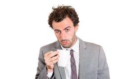 Un homme d'affaires somnolent fatigué tenant une tasse de boisson Photographie stock libre de droits