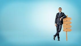 Un homme d'affaires sur le fond bleu se penche en passant sur une petite enseigne en bois montrant la manière dans seulement une  photographie stock libre de droits
