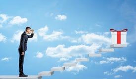 Un homme d'affaires sur le fond de ciel regardant un escalier gris pour voir un giftbox blanc avec un arc rouge Images stock