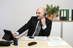 Un homme d'affaires téléphone tandis qu'il recherche les informations sur son comprimé photos stock
