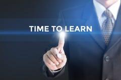 Un homme d'affaires tenant un signe blanc avec l'heure de message d'apprendre Photo libre de droits