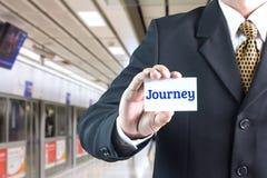 Un homme d'affaires tenant un signe blanc avec le message voyage Photos stock