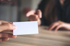 Un homme d'affaires tenant une carte de visite professionnelle de visite vide avec la femme d'affaires Photographie stock