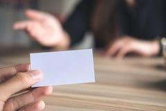 Un homme d'affaires tenant une carte de visite professionnelle de visite vide avec la femme d'affaires Photographie stock libre de droits