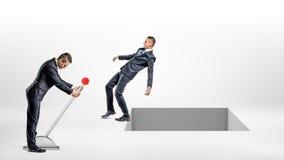 Un homme d'affaires tourne un grand commutateur de levier tandis qu'un autre homme retombe à une perforation rectangulaire ouvert Photographie stock libre de droits