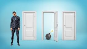 Un homme d'affaires triste avec sa tête abaissée se tient près de trois portes où on est ouvert et montre une bombe allumée Photographie stock