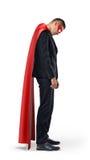 Un homme d'affaires triste dans un cap rouge de super héros se tenant avec ses épaules s'est effondré et regardant vers le bas Photos libres de droits