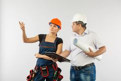 Un homme d'architecte portant les modèles de révision de femme d'un casque antichoc ou de constructeur de casque et de collègue photographie stock