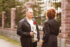 Un homme d'une cinquantaine d'années donne une rose à une femme image libre de droits