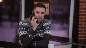Un homme dans un café potable de barre confortable à la table et aux utilisations le smartphone banque de vidéos