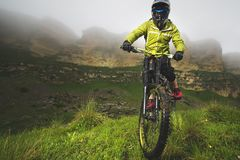 Un homme dans un casque de montagne montant un vélo de montagne monte autour de la belle nature par temps nuageux downhill photos libres de droits