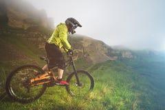 Un homme dans un casque de montagne montant un vélo de montagne monte autour de la belle nature par temps nuageux downhill photo stock