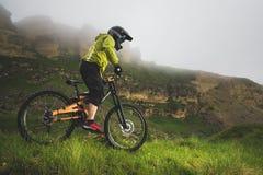 Un homme dans un casque de montagne montant un vélo de montagne monte autour de la belle nature par temps nuageux downhill image stock