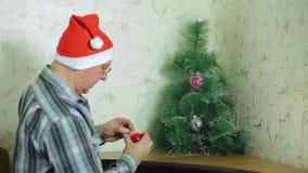 Un homme dans un chapeau de Santa Claus assortit des boules de vacances pour décorer un arbre de Noël banque de vidéos