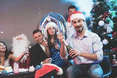 Un homme dans un chapeau de Santa Claus ouvre une bouteille de champagne Les amis du ` un s d'homme s'asseyent à côté de lui et d Photos libres de droits