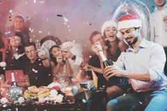 Un homme dans un chapeau de Santa Claus ouvre une bouteille de champagne Les amis du ` un s d'homme s'asseyent à côté de lui et d Images libres de droits