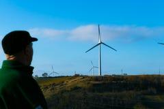 Un homme dans un chapeau regarde les turbines de vent de rotation contre le ciel bleu image stock