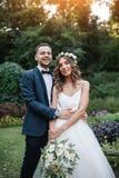 Un homme dans un costume étreignant son amie dehors, la jeune mariée et le g Photos libres de droits