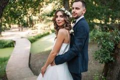 Un homme dans un costume étreignant son amie dehors, la jeune mariée et le g Image stock