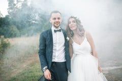 Un homme dans un costume étreignant son amie dehors, la jeune mariée et le g Photo libre de droits