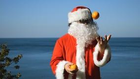 Un homme dans un costume de Santa Claus jongle des mandarines sur le bord de la mer Course et vacances banque de vidéos