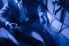 Un homme dans un costume se situe dans un bain de l'eau photos libres de droits