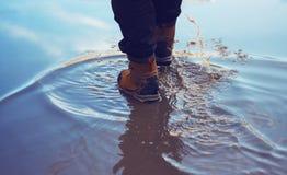Un homme dans des chaussures imperméables croise l'étang images stock