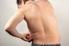 Un homme dans des jeans avec un gros ventre et un torse nu sur un fond blanc photo libre de droits