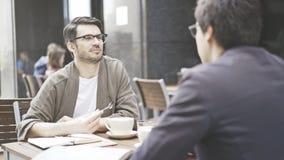 Un homme dans des lunettes écoute son ami au café dehors Photos stock